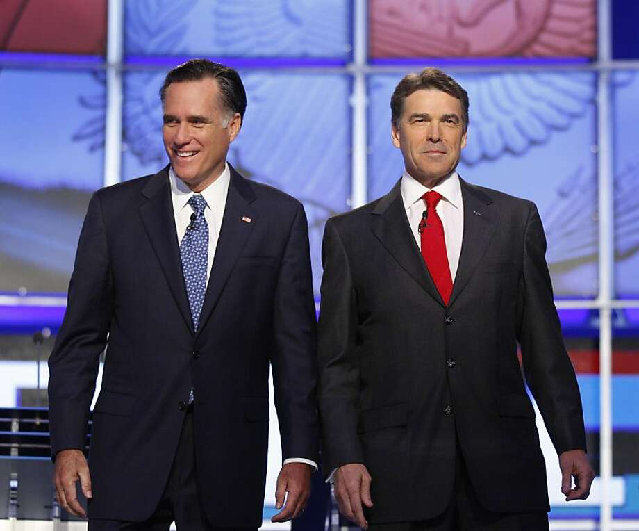 In this photo taken Oct. 18, 2011, Republican presidential candidates, former Massachusetts Gov. Mitt Romney, left, and Texas Gov. Rick Perry, take part in a Republican presidential debate in Las Vegas. Romney and Perry now are using tough new language online and on the campaign trail to undermine each other's credibility and values. The amped-up rhetoric signals a more aggressive phase in the race and sets the tone in the ten weeks left before the 2012 nominating contest begins in Iowa in early January. (AP Photo/Isaac Brekken) Photo: Isaac Brekken, AP