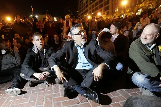 John Avalos, center, a member of the San Francisco Board of Supervisors and a candidate for Mayor, sits in support of Occupy San Francisco with protesters in San Francisco, Wednesday, Oct. 26, 2011. San Francisco officials are warning anti-Wall Street protesters camped out in a city plaza that they face arrest if they continue to stay there around the clock. In a notice distributed on Tuesday, Police Chief Greg Suhr said the protesters in Justin Herman Plaza could be arrested on a variety of sanitation or illegal camping violations although police are not saying when that could occur. (AP Photo/Jeff Chiu) Photo: Jeff Chiu, AP