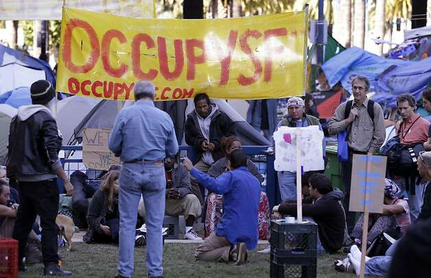 Demonstrators meet at an encampment of Occupy San Francisco protest in downtown San Francisco, Wednesday, Oct. 26, 2011. San Francisco officials are warning anti-Wall Street protesters camped out in a city plaza that they face arrest if they continue to stay there around the clock. In a notice distributed on Tuesday, Police Chief Greg Suhr said the protesters in Justin Herman Plaza could be arrested on a variety of sanitation or illegal camping violations although police are not saying when that could occur. (AP Photo/Paul Sakuma) Photo: Paul Sakuma, AP