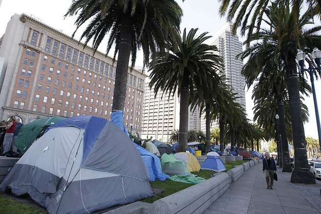 A man walks by an encampment of Occupy San Francisco protest in downtown San Francisco, Wednesday, Oct. 26, 2011. San Francisco officials are warning anti-Wall Street protesters camped out in a city plaza that they face arrest if they continue to stay there around the clock. In a notice distributed on Tuesday, Police Chief Greg Suhr said the protesters in Justin Herman Plaza could be arrested on a variety of sanitation or illegal camping violations although police are not saying when that could occur. (AP Photo/Paul Sakuma) Photo: Paul Sakuma, AP