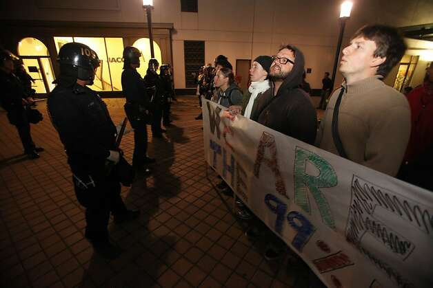 Oakland Occupy  protestors form a line opposing the police at the Frank Ogawa Plaza  on Tuesday. Oct. 25, 2011 in Oakland, Calif.   Police in riot gear began clearing anti-Wall Street protesters on Tuesday morning from the plaza in front of Oakland's City Hall where they have been camped out for about two weeks.    City officials had originally been supportive of the protesters, but the city later warned the protesters that they were breaking the law and could not stay in the encampment overnight. (AP Photo/Bay Area News Group, Jane Tyska) Photo: Jane Tyska, The Oakland Tribune Via AP