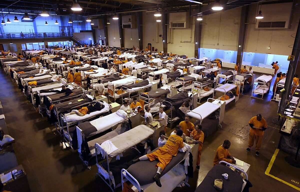 """FILE - In this May 20, 2009 file photo, several hundred inmates crowd the gymnasium at San Quentin prison in San Quentin, Calif. The Supreme Court on Monday, May 23, 2011, endorsed a court order requiring California to cut its prison population by tens of thousands of inmates to improve health care for those who remain behind bars. The court said in a 5-4 decision that the reduction is """"required by the Constitution"""" to correct longstanding violations of inmates' rights. The order mandates a prison population of no more than 110,000 inmates, still far above the system's designed capacity. (AP Photo/Eric Risberg, File)"""