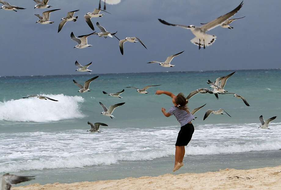 A child plays with seagulls at the beach in Playa del Carmen, Mexico, during the approach of Tropical Storm Rina Thursday Oct. 27, 2011. Rina was downgraded from a hurricane to a tropical storm Thursday afternoon after many tourists had already cut short their trips to Cancun and other Caribbean resorts ahead of what once threatened to be a Category 3 storm. (AP Photo/Marco Ugarte) Photo: Marco Ugarte, AP