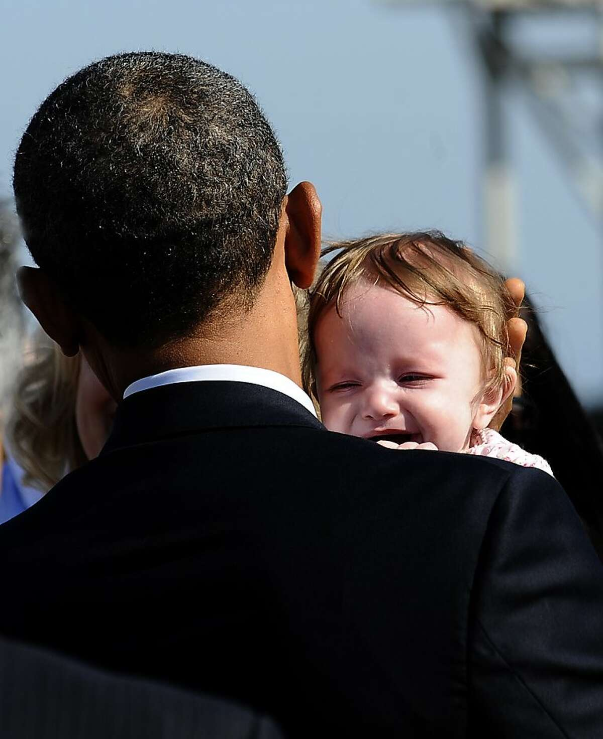 US President Barack Obama holds a baby as he greets people at San Francisco International Airport in San Francisco, California, on October 25, 2011. Obama unveiled a stopgap plan Monday to ease the bite of the real estate crisis for cash-strapped homeowners while attacking Congress for blocking spending to create more jobs. Thwarted by Republican opposition to his bigger jobs and stimulus package, Obama has shifted tactics by looking for action he can take without congressional approval to provide at least modest economic relief. AFP Photo/Jewel Samad (Photo credit should read JEWEL SAMAD/AFP/Getty Images)
