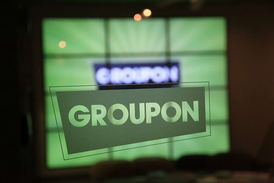 The Groupon logo etched in glass in the lobby of the online coupon company's Chicago offices Thursday, Sept. 22, 2011.  Online coupon seller Groupon Inc. is discounting its expectations for its first stock offering, reported Friday, Oct. 21, 2011. The company, which offers consumers daily discounts targeted to their city and preferences, now expects net proceeds of about $478.8 million from its initial public offering of 30 million shares. (AP Photo/Charles Rex Arbogast)  Ran on: 10-26-2011 Groupon accuses two former sales managers of taking trade secrets to a competing venture. Photo: Charles Rex Arbogast, AP