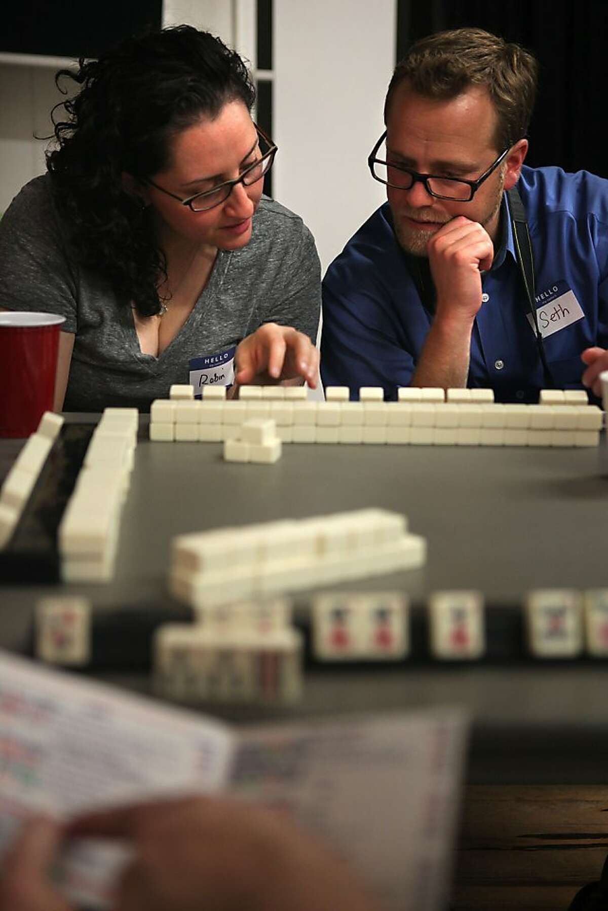 Robin Handwerker (left), and Seth Linden (right) partner up while learning to play the game of Mahjong in a building at Dogpatch in San Francisco, California, on Tuesday, September 27, 2011. Seth just started playing about a week ago.