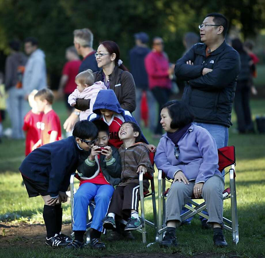 Gordon Yee, 9, left, Dalan Choy, 9, Riley Gee, 7, and Rafael Cenzano, rear, play games on an old iPhone 3G during their siblings' soccer game at Little Rec soccer fields in Golden Gate Park, Saturday, October 22, 2011, while Diane Yee watches to the right. Photo: Judy Walgren, The Chronicle