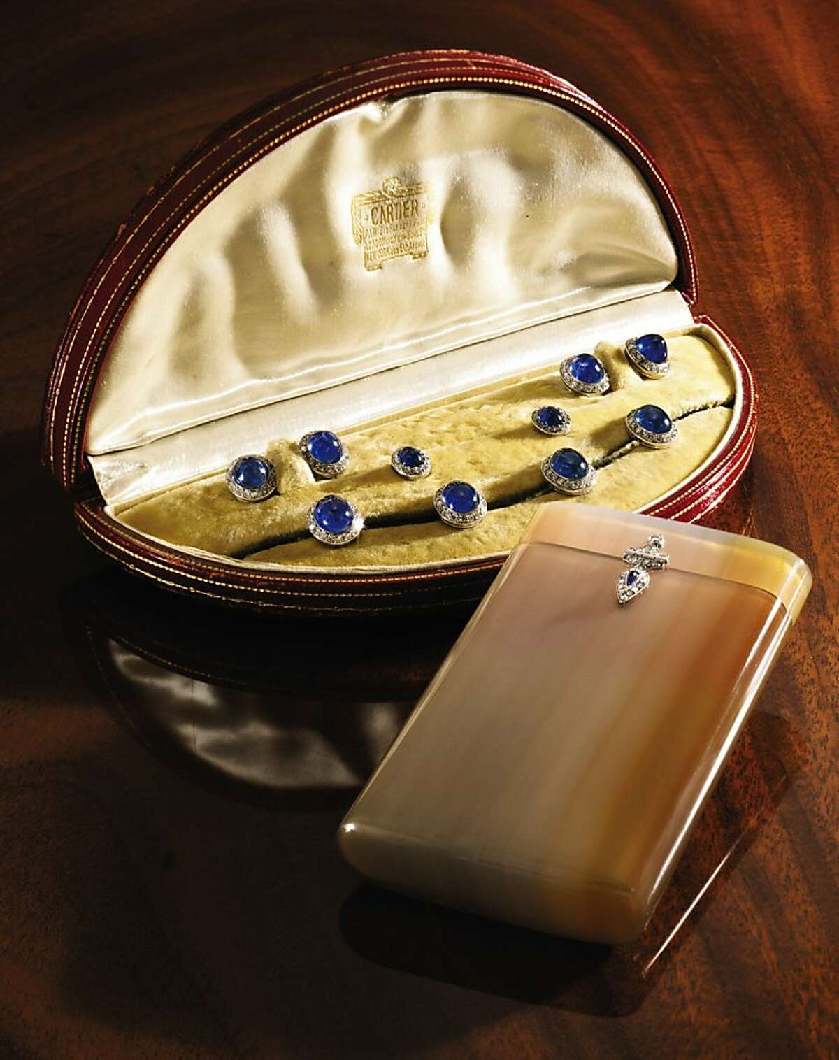Pieces from the holdings of the late objet d'art collector John Traina of San Francisco will be auctioned at Sotheby's in New York on Dec. 7. They include this platinum, agate, sapphire and diamond cigarette case by Cartier of New York, circa 1920 (estimated value $5,000-7,000.) Platinum, Cabochon Sapphire and Diamond Dess Set, Cartier, Paris, Circa 1920, comprising a pair of cufflinks, four buttons and two studes, in a signed and fitted box. (Est. $10,000-15,000)