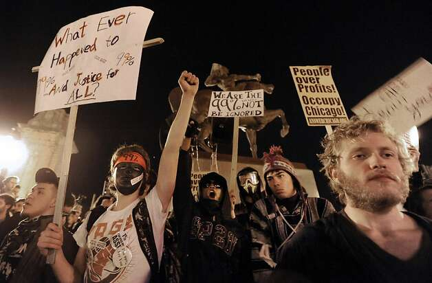 Protesters during an Occupy Chicago march and protest at Grant Park in Chicago, late Saturday Oct. 22, 2011. Demonstrators of the anti-Wall Street group Occupy Chicago stood their ground in a downtown park and defied police orders to clear the area, prompting police to make more than a dozen arrests early Sunday.  (AP Photo/Paul Beaty) Photo: Paul Beaty, AP