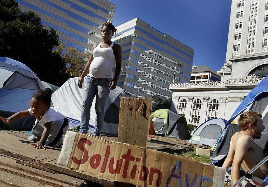 People make their way down Solution Avenue in the tent city in front of City Hall. Despite a police order to vacate the property, the Occupy Oakland protesters spent the day around their large campsite in front of Oakland City Hall Sunday October 23, 2011. Photo: Brant Ward, The Chronicle