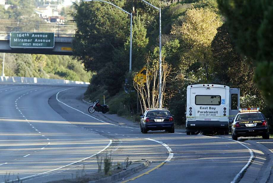 The California Highway Patrol and Alameda County Sheriffs Department shutdown eastbound I-580 at 150th Avenue as they investigate a crash between a motorcycle and an East Bay Paratransit bus in San Lorenzo, Calif. on Saturday Oct. 22, 2011. A Hell's Angels motorcyclist was killed in the crash which is being investigated as a homicide according to California Highway Patrol officer Sgt. Trent Cross. The van driver is suspected of intentionally hitting the motorcyclist who was dragged several miles under the van.  (Anda Chu/Bay Area News Group) Photo: Anda Chu, AP