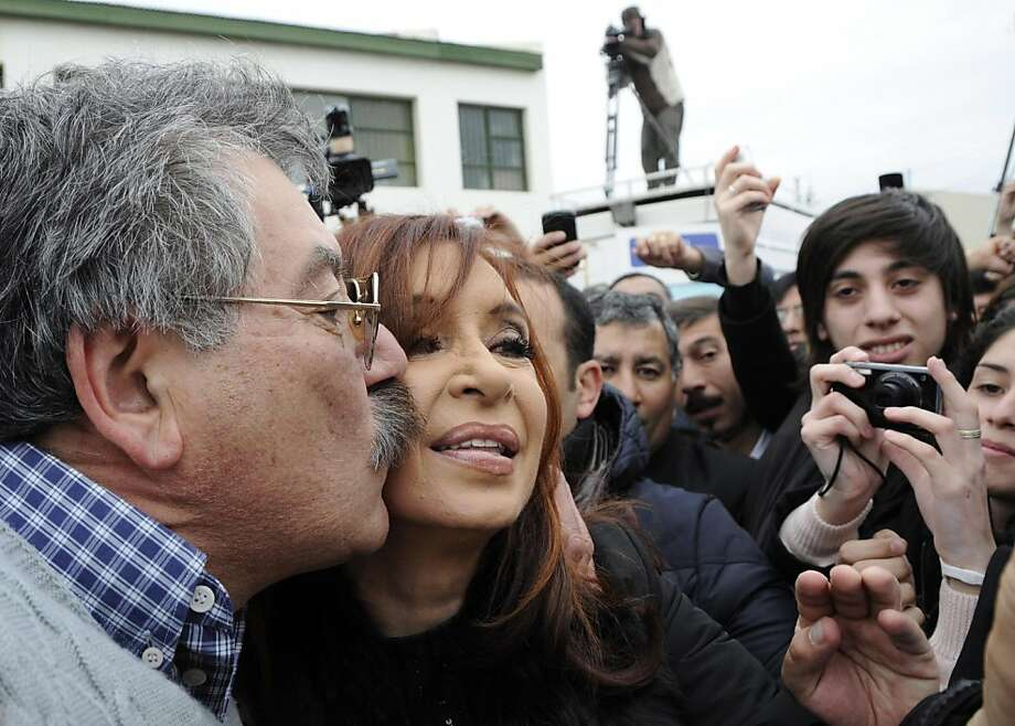 Argentina's President Cristina Fernandez poses for pictures with supporters after voting in the general elections in Rio Gallegos, Argentina, Sunday Oct. 23, 2011. Fernandez appeared to be headed for a landslide victory over six rivals as Argentines voted on Sunday. If she does win, she'll be the first woman re-elected as president in Latin America. (AP Photo/Francisco Munoz) Photo: Francisco Munoz, AP