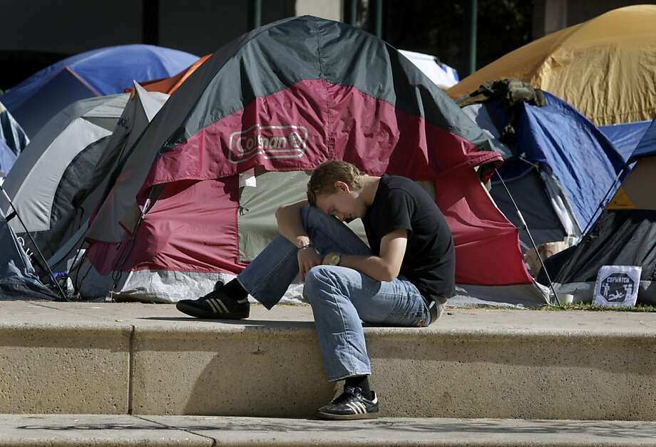 A young man rests on the steps of Frank Ogawa Plaza in front of the Occupy Oakland tent city at City Hall in Oakland, Calif. on Tuesday, Oct. 18, 2011. A second encampment is now set up at Snow Park across from Lake Merritt. Photo: Paul Chinn, The Chronicle