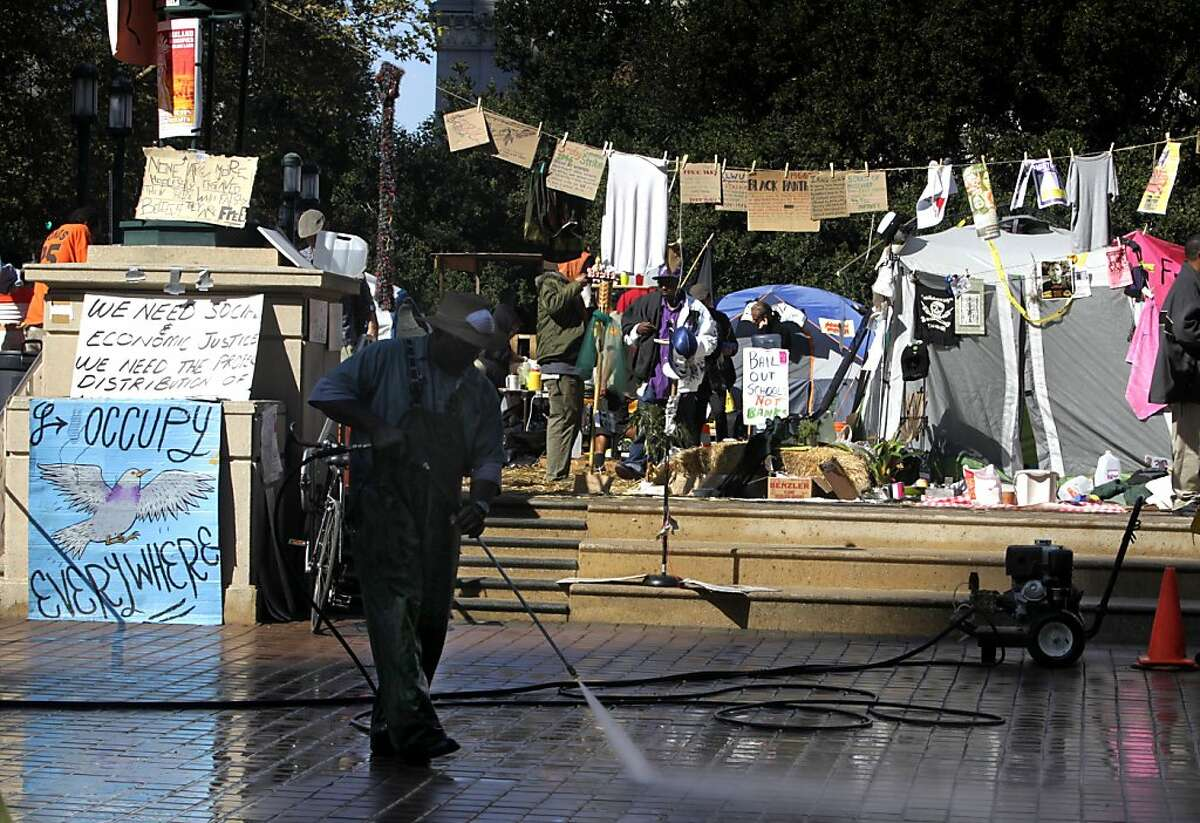 A city worker cleans Frank Ogawa Plaza as protesters remain at the Occupy Oakland tent city for a second week at City Hall in Oakland, Calif. on Tuesday, Oct. 18, 2011. A second encampment is now set up at Snow Park across from Lake Merritt.