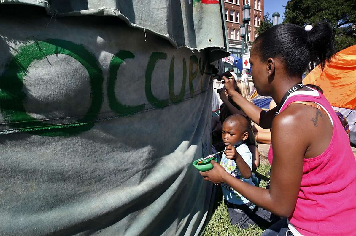 Torricka Wilson and her son Toriano Adger, 3, decorate a tent at the Occupy Oakland tent city in Frank Ogawa Plaza at City Hall in Oakland, Calif. on Tuesday, Oct. 18, 2011. A second encampment is now set up at Snow Park across from Lake Merritt.