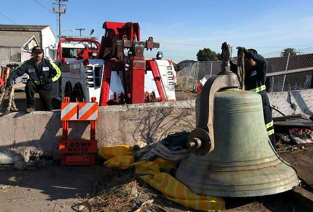 Tow truck operators hook up the stolen Bell taken last week from the front of St. Mary's Cathedral in San Francisco. The bell was coved with tarps at the end of 9th street in front of 21st Century Recycling in west Oakland Wednesday Oct 26, 2011. Photo: Lance Iversen, The Chronicle