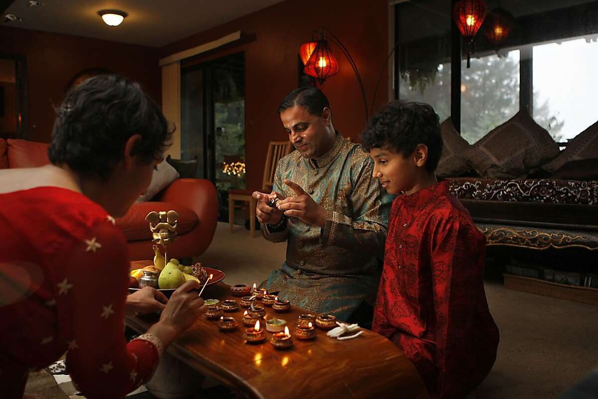 Shoshana Wolff (left), Sachin Chopra (middle), chef/owner of All Spice, with their nephew Ahab Chopra (right), 11 years old from Mountain View, lighting diyas on the altar at home in Woodside, Calif., on Monday, October 10, 2011. Diwali, the Indian festival of lights will be on Oct. 26.