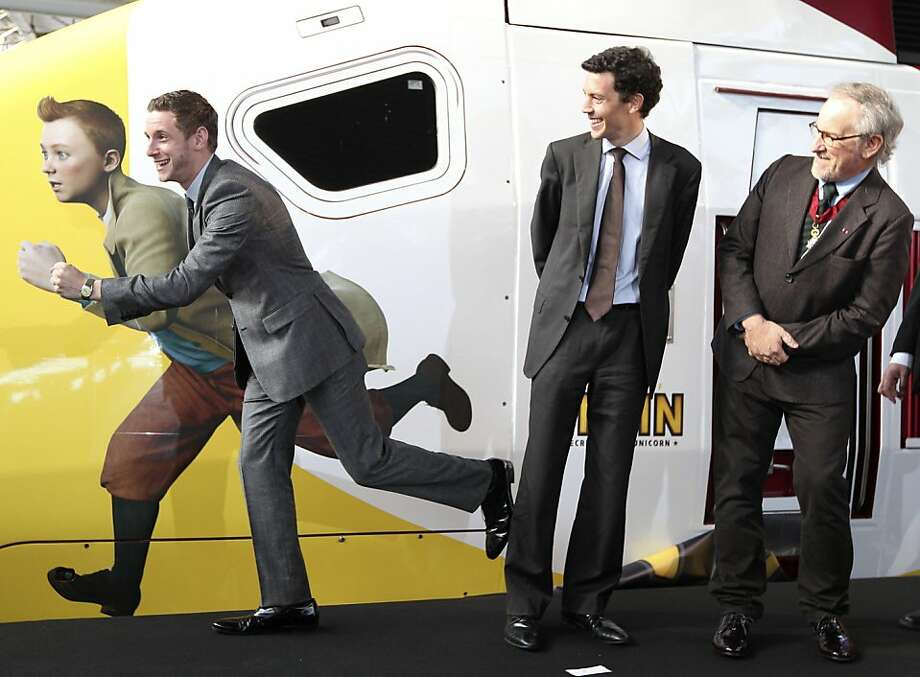"""British actor Jamie Bell poses next to Belgian cartoon hero Tintin, depicted on a special high speed Thalys train boarding for Paris, as movie director Steven Spielberg, right, and Thalys high speed train service CEO Franck Gervais look at him, after Spielberg attended the world premiere of the Belgian cartoon hero Tintin movie """"The Adventures of Tintin: Secret of the Unicorn"""", in Brussels, Saturday, Oct. 22, 2011. (AP Photo/Yves Logghe)  Ran on: 10-26-2011 Actor Jamie Bell (left), Thalys train service CEO Franck Gervais and Steven Spielberg in Brussels. Photo: Yves Logghe, AP"""