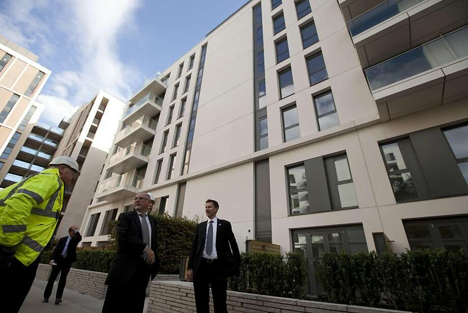 Britain's Culture Secretary Jeremy Hunt, right, and the Chief Executive-elect of the Olympic Delivery Authority (ODA) Dennis Hone, second right, stand by structurally completed apartment blocks during their visit to the Olympic Village in the Olympic Park in east London, Tuesday, Oct. 25, 2011.  So far 2,300 apartments at the Olympic Village have been completed and the final number will be 2,818.  (AP Photo/Matt Dunham-Pool)  Ran on: 10-26-2011 Britain's Culture Secretary Jeremy Hunt (right) and the Olympic Delivery Authority chief executive Dennis Hone stand in front of apartment blocks at the Olympic Village. Ran on: 10-26-2011 Britain's Culture Secretary Jeremy Hunt (right) and the Olympic Delivery Authority chief executive Dennis Hone stand in front of apartment blocks at the Olympic Village. Photo: Matt Dunham, AP