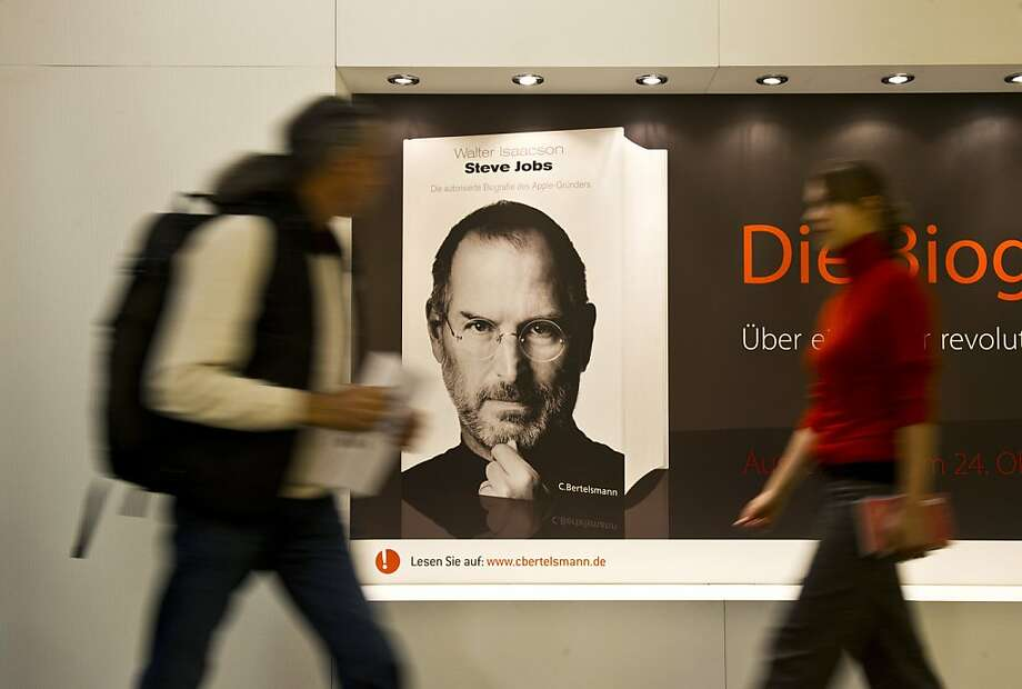Visitors walk past an ad for a biography of Apple founder Steve Jobs, who died October 5, 2011, at the 63rd Frankfurt Book Fair October 11, 2011. This year's edition of the largest book fair in the world takes place from October 12 - 16, and features Iceland as guest of honour.  AFP PHOTO / JOHN MACDOUGALL (Photo credit should read JOHN MACDOUGALL/AFP/Getty Images) Photo: John Macdougall, AFP/Getty Images