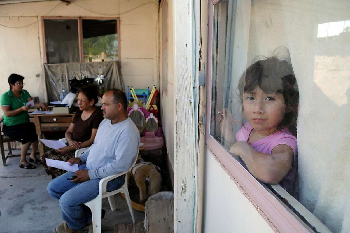 Ana Sanchez ´ granddaughter peeks out the window during committee meeting at St Anthonys Mobile Home Park. Carlos Puma for California Watch