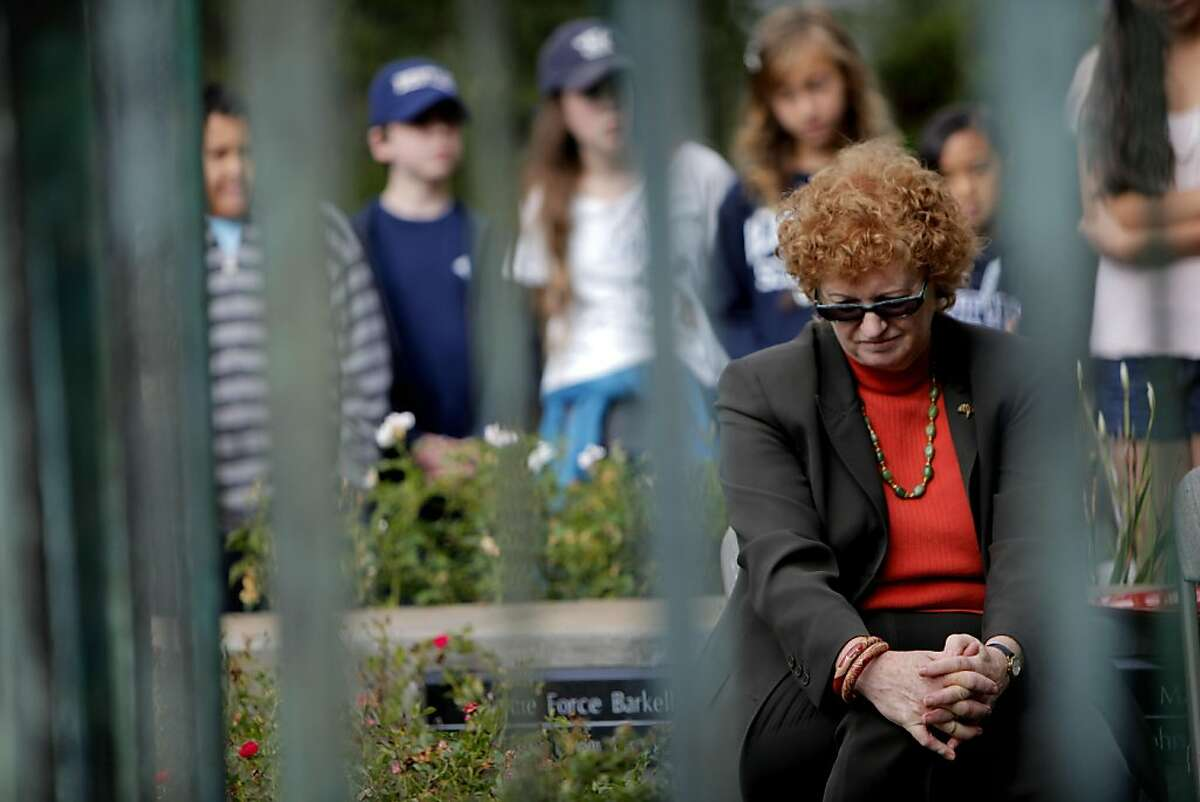 Sue Piper bows her head as she sits in front of the Firestorm Memorial Garden Sculpture during the ceremony with Oakland's Mayor Jean Quan and suvivors to commemorate the 20th anniversary of the 1991 Oakland Firestorm, Thursday October 20, 2011, at the Firestorm Memorial Garden in Oakland, Calif. Piper was one of the many who lost their home in the fire.