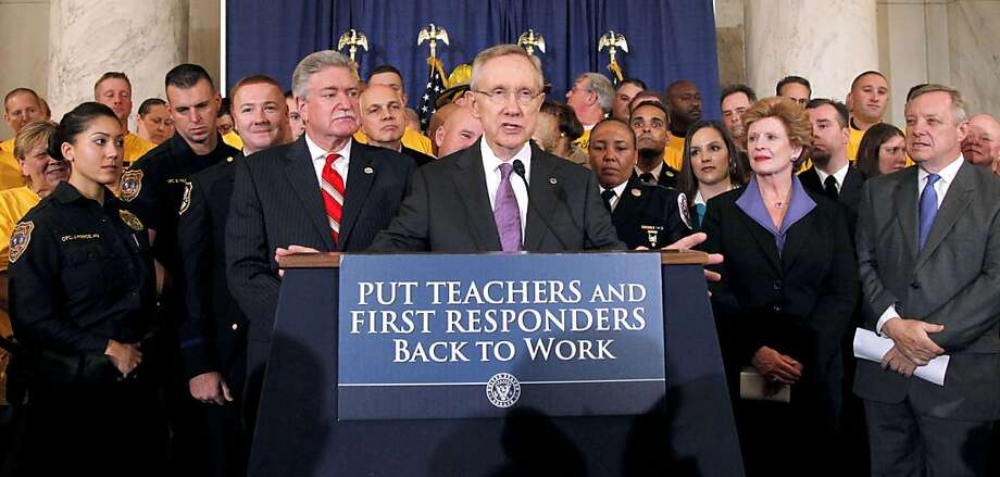Senate Majority Leader Harry Reid of Nev. speaks during a news conference to urging the passage of the Teachers and First Responders Back to Work Act, Wednesday, Oct. 19, 2011, on Capitol Hill in Washington. He is joined by Senate Majority Whip Richard Durbin of Ill., right, Sen. Debbie Stabenow, D-Mich., second from right, and others.  (AP Photo/Haraz N. Ghanbari) Photo: Haraz N. Ghanbari, AP