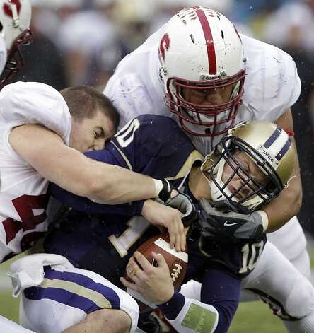Washington quarterback Jake Locker (10) is sacked by Stanford's Chase Thomas, left, and Matthew Masifilo in the first half during an NCAA college football game Saturday, Oct. 30, 2010, in Seattle. (AP Photo/Elaine Thompson)  Ran on: 10-31-2010 Washington quarterback Jake Locker is sacked by Stanford's Chase Thomas (left) and Matthew Masifilo in the first half. Ran on: 10-31-2010 Washington quarterback Jake Locker is sacked by Stanford's Chase Thomas (left) and Matthew Masifilo in the first half. Photo: Elaine Thompson, AP