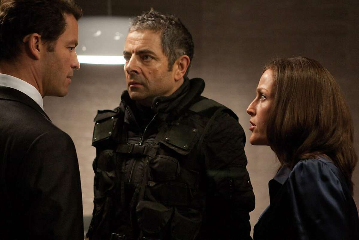 """Agent Ambrose (Dominic West, left), Johnny English (Rowan Atkinson, center) and Director Thornton (Gillian Anderson) in the comedy/spy thriller, """"Johnny English Reborn."""" In the film, Atkinson returns to the role of the improbable secret agent who doesn't know fear or danger. (Giles Keyte/Courtesy Universal Pictures/MCT)"""