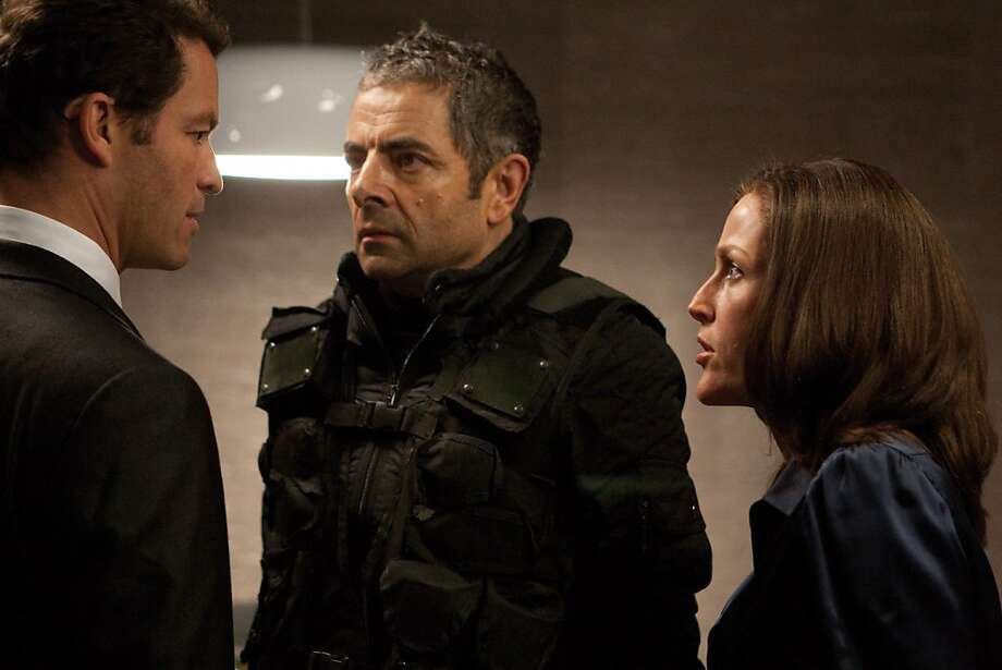 "Agent Ambrose (Dominic West, left), Johnny English (Rowan Atkinson, center) and Director Thornton (Gillian Anderson) in the comedy/spy thriller, ""Johnny English Reborn."" In the film, Atkinson returns to the role of the improbable secret agent who doesn't know fear or danger. (Giles Keyte/Courtesy Universal Pictures/MCT) Photo: Handout, MCT"