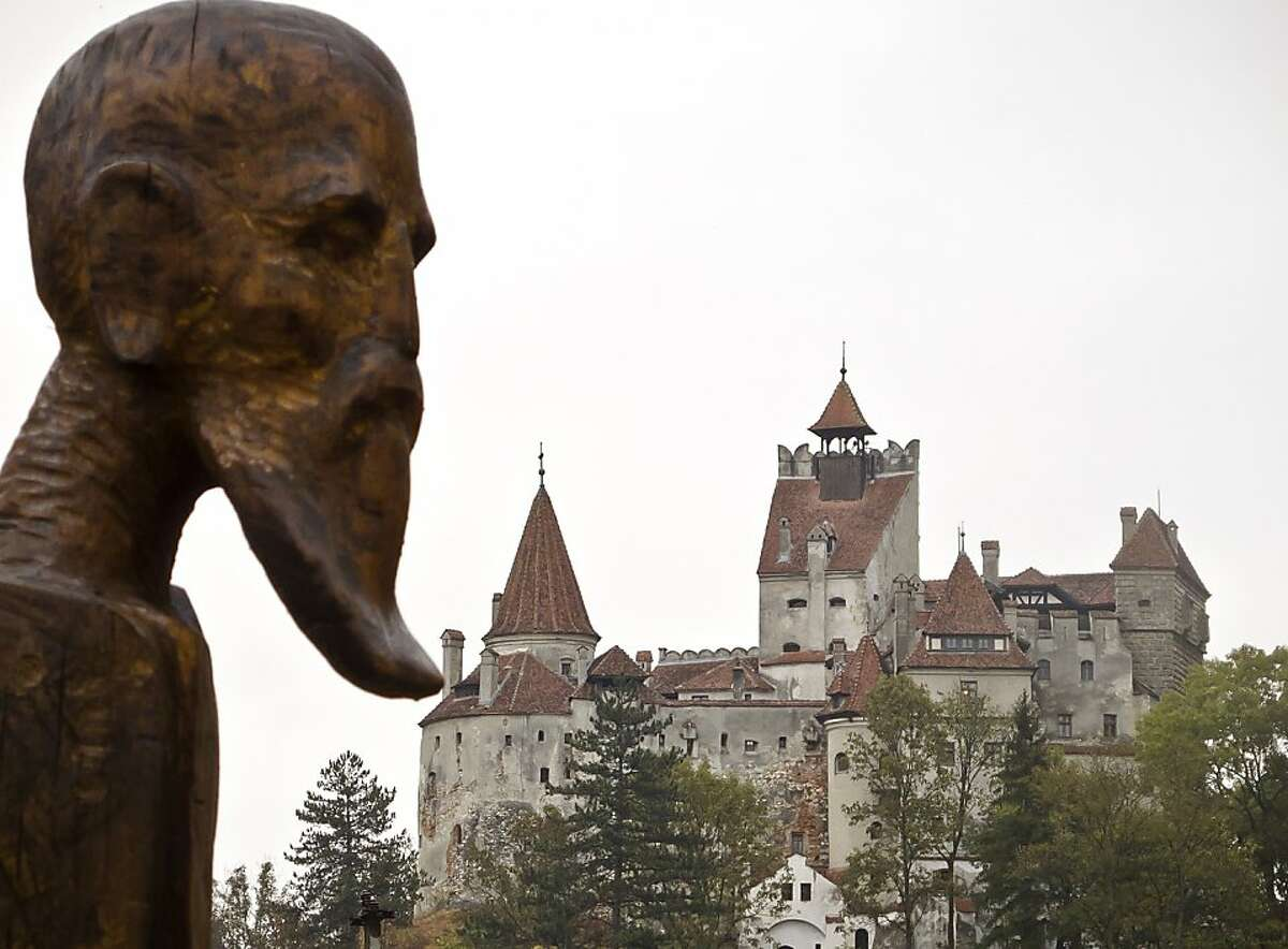 A sculpture commemorating Petru Darascu, a Romanian priest who survived several Communist prisons, by Ovidiu Nicolae Popa is backdropped by the Gothic Bran Castle, better known as Dracula Castle, in Bran, in Romania's central Transylvania region, Saturday, Oct. 8, 2011. The castle attracts numerous visitors in all seasons who want to experience first hand the atmosphere and landscape depicted in Bram Stoker's famous novel Dracula. (AP Photo/Selcan Hacaoglu) Ran on: 10-23-2011 A statue of a Romanian priest is backdropped by the Gothic Bran Castle in Romania's Transylvania region.