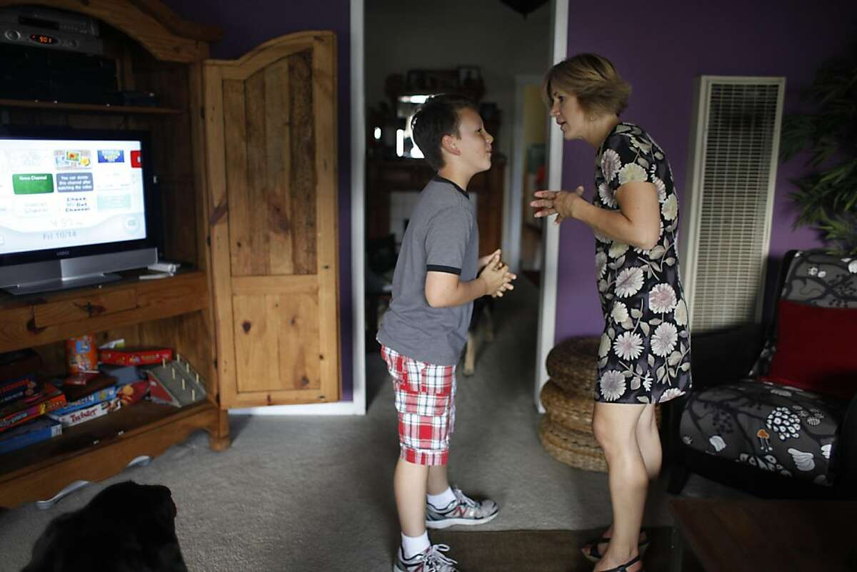 Jean McGuinness tells her son, Seamus (left), 10 to get into his baseball uniform for baseball practice at their home in Alameda, Calif., on Friday, October 14, 2011.