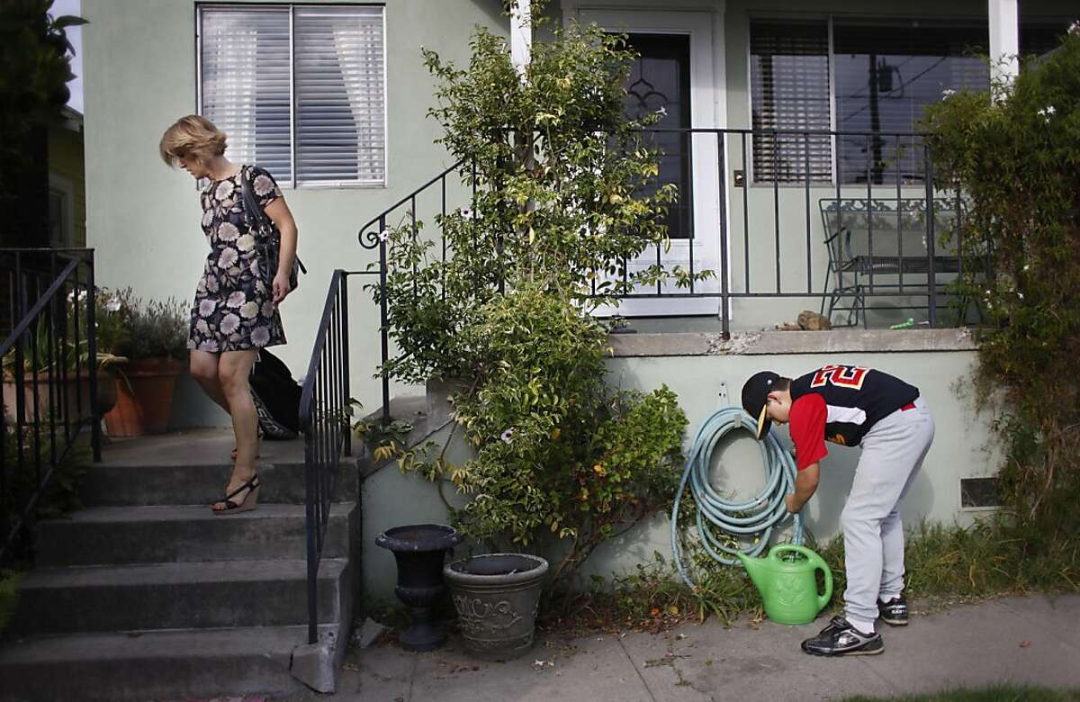 Jean McGuinness (l to r) carries her sons baseball gear to her car as her son, Seamus, 10, fills a watering can to water plants as they head out from their home to baseball practice in Alameda, Calif., on Friday, October 14, 2011. Ran on: 10-18-2011 Jean McGuinness says that refinancing could help her provide more extracurricular activities, camps and sports for her son, Seamus, 10. Ran on: 10-18-2011 Jean McGuinness says that refinancing could help her provide more extracurricular activities, camps and sports for her son, Seamus, 10.