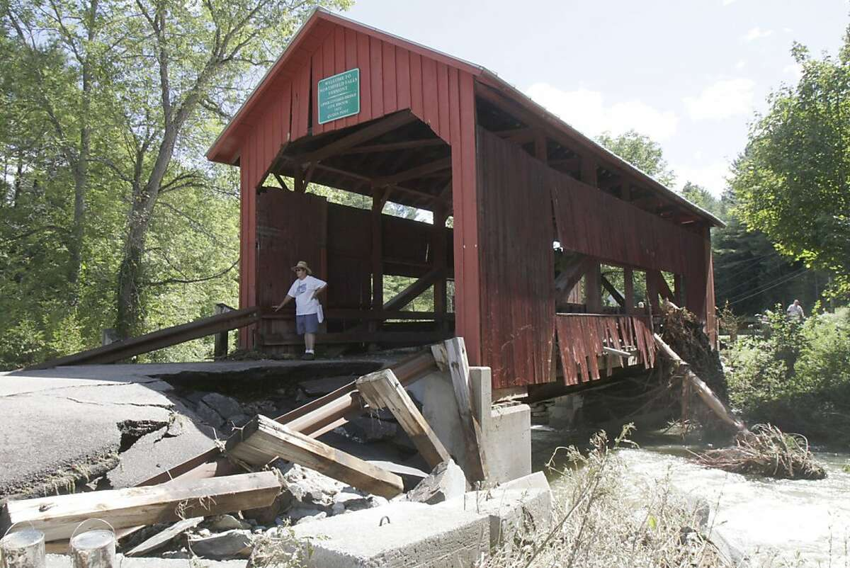 In this Aug. 29, 2011 photo, a visitor stands at the damaged historic covered bridge in Northfield, Vt. Flash flooding caused by Tropical Storm Irene damaged the bridge. (AP Photo/Toby Talbot) Ran on: 10-23-2011 Photo caption Dummy text goes here. Dummy text goes here. Dummy text goes here. Dummy text goes here. Dummy text goes here. Dummy text goes here. Dummy text goes here. Dummy text goes here.###Photo: bridges16_PH1314316800AP###Live Caption:In this Aug. 29, 2011 photo, a visitor stands at the damaged historic covered bridge in Northfield, Vt. Flash flooding caused by Tropical Storm Irene damaged the bridge.###Caption History:In this Aug. 29, 2011 photo, a visitor stands at the damaged historic covered bridge in Northfield, Vt. Flash flooding caused by Tropical Storm Irene damaged the bridge. (AP Photo-Toby Talbot)###Notes:###Special Instructions:AN AUG. 29, 2011 PHOTO
