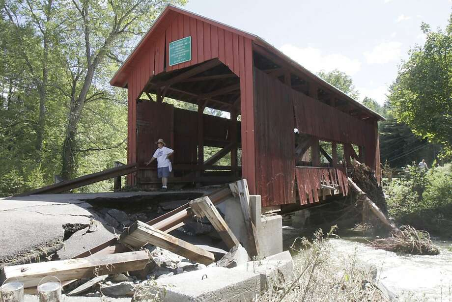 In this Aug. 29, 2011 photo, a visitor stands at the damaged historic covered bridge in Northfield, Vt. Flash flooding caused by Tropical Storm Irene damaged the bridge. (AP Photo/Toby Talbot)  Ran on: 10-23-2011 Photo caption Dummy text goes here. Dummy text goes here. Dummy text goes here. Dummy text goes here. Dummy text goes here. Dummy text goes here. Dummy text goes here. Dummy text goes here.###Photo: bridges16_PH1314316800AP###Live Caption:In this Aug. 29, 2011 photo, a visitor stands at the damaged historic covered bridge in Northfield, Vt. Flash flooding caused by Tropical Storm Irene damaged the bridge.###Caption History:In this Aug. 29, 2011 photo, a visitor stands at the damaged historic covered bridge in Northfield, Vt. Flash flooding caused by Tropical Storm Irene damaged the bridge. (AP Photo-Toby Talbot)###Notes:###Special Instructions:AN AUG. 29, 2011 PHOTO Photo: Toby Talbot, AP