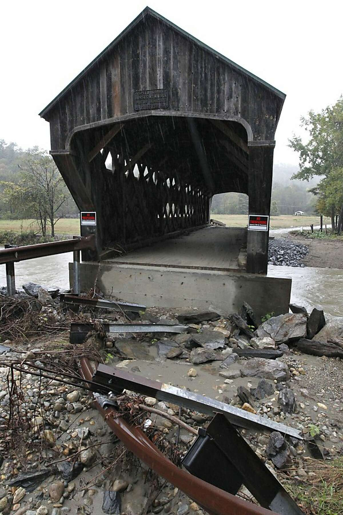 In this Thursday, Sept. 29, 2011 photo the flood-damaged Worrall covered bridge spans the Williams River, in Rockingham, Vt. The Worrall bridge, constructed in the late 19th century, stands downstream from where the Bartonsville covered bridge once stood in Rockingham before it was destroyed in August of 2011 by flooding from tropical storm Irene. (AP Photo/Steven Senne)