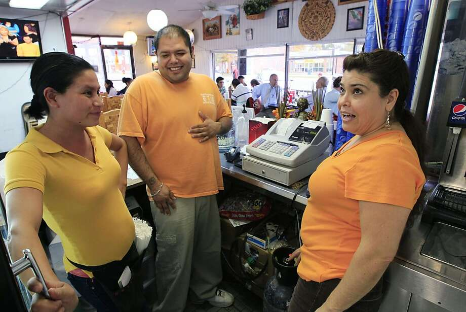 In a Wednesday, Oct. 12, 2011 photo, owner Marta Guzman, right, speaks with her son, Francisco Mejia and server Maria Velazquez, left,  at Taqueria Mixteca restaurant, in Dayton, Ohio. The restaurant is one of four restaurants in southwest Ohio started and owned by the same Mexican family. It's the kind of success story that leaders in Dayton think offers hope for an entire city. It has adopted a plan not only to encourage immigrants to come and feel welcome, but also to use them to help pull out of an economic tailspin.  (AP Photo/Al Behrman) Photo: Al Behrman, AP