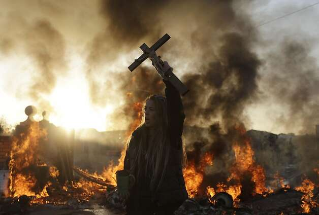 An Irish traveler resident holds up a cross for the media, in front of a burning barricade during evictions at the Dale Farm travellers site, near Basildon England, 30 miles (50 kilometers) east of London, Wednesday, Oct. 19, 2011.  Police in riot gear used sledgehammers to clear the way for the eviction of a community of Irish Travellers from a site where they have lived illegally for a decade.  A large force of police and bailiffs faced resistance from several dozen residents and supporters who threw bricks and struggled with officers.  (AP Photo/Matt Dunham) Ran on: 10-23-2011 Left: An Irish Traveler holds up a cross in front of a burning barricade during evictions at Dale Farm, 30 miles east of London. Photo: Matt Dunham, AP
