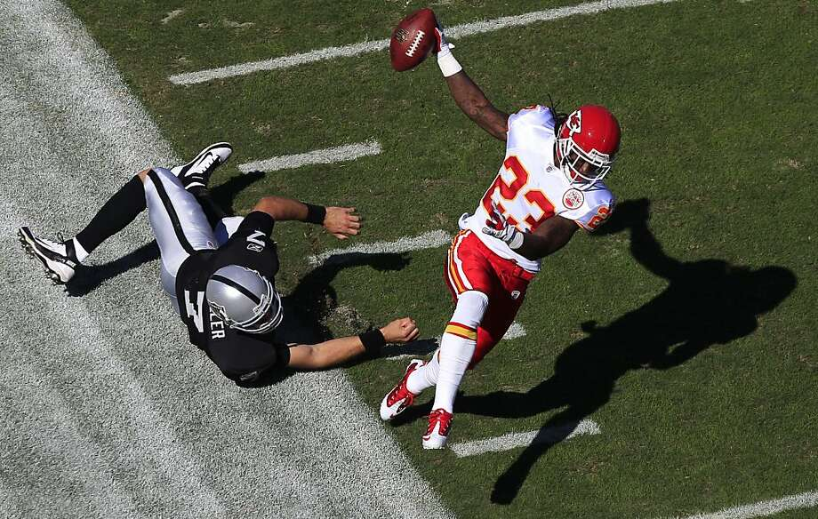 Kansas City Chiefs free safety Kendrick Lewis (23) runs past a diving Oakland Raiders quarterback Kyle Boller (7) on a 59-yard interception for a touchdown in the first quarter of an NFL football game in Oakland, Calif., Sunday, Oct. 23, 2011. (AP Photo/Marcio Jose Sanchez) Photo: Marcio Jose Sanchez, AP