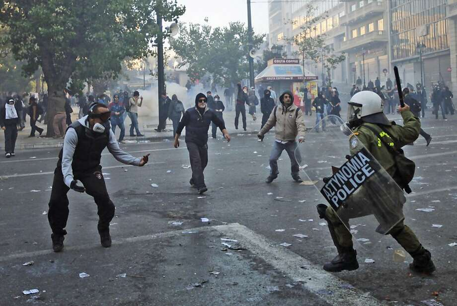Protesters challenge a Greek riot police officer, during clashes in central Athens, Wednesday, Oct. 19, 2011. Greek anger over new austerity measures and layoffs erupted into violence Wednesday, as demonstrators hurled chunks of marble and gasoline bombs and riot police responded with tear gas and stun grenades that echoed across Athens' main square. (AP Photo/Lefteris Pitarakis) Photo: Lefteris Pitarakis, AP