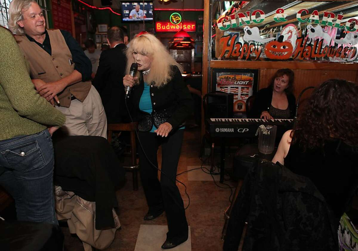 Carol Doda, who at one time was the most famous stripper in the world, sings at Gino and Carlo's Bar in San Francisco Calif., on October 5, 2011. One of Doda's friends, Dave Poindexter of San Francisco leans against the bar as he listens to her perform accompanied by Maddaline Edstrom on the piano.