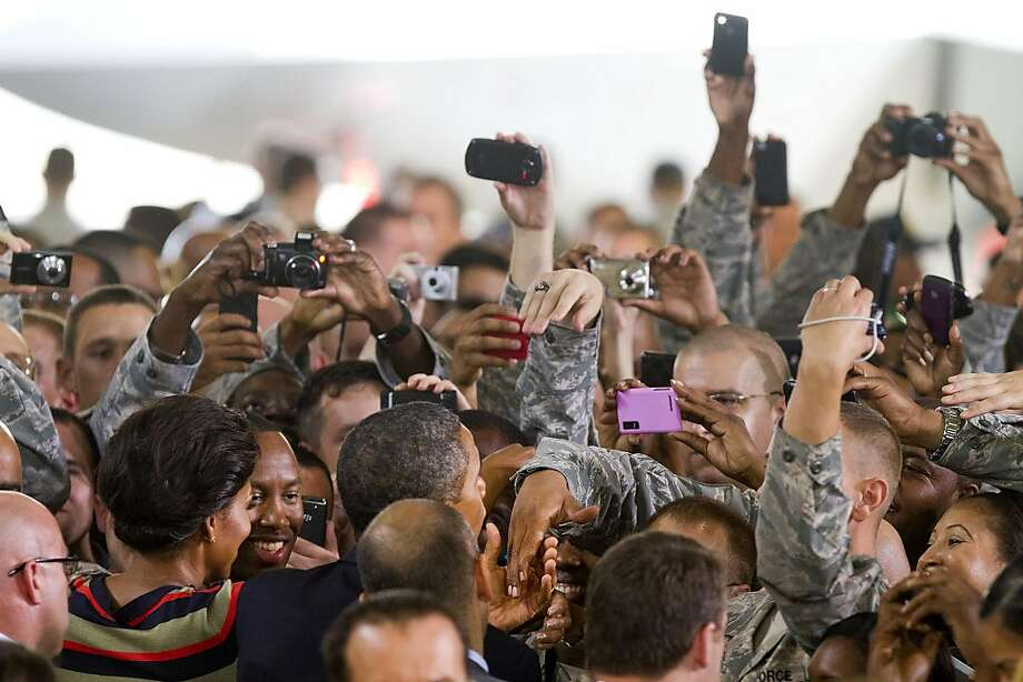 President Barack Obama and first lady Michelle Obama shake hands with members of the Air Force and Army after the President's remarks at the 94th Fighter Squadron Hangar, the Joint Base Langley-Eustis Wednesday, Oct. 19, 2011 in Hampton, Va. Heralding a splash of good news on jobs, President Barack Obama on Wednesday praised a series of companies that have promised to hire 25,000 veterans or military spouses within two years, calling it a sign of patriotism and business savvy. He pushed his economic agenda anew to a military audience, this time with first lady Michelle Obama at his side.   (AP Photo/The Virginian-Pilot, Bill Tiernan)  MAGS OUT Photo: Bill Tiernan, AP