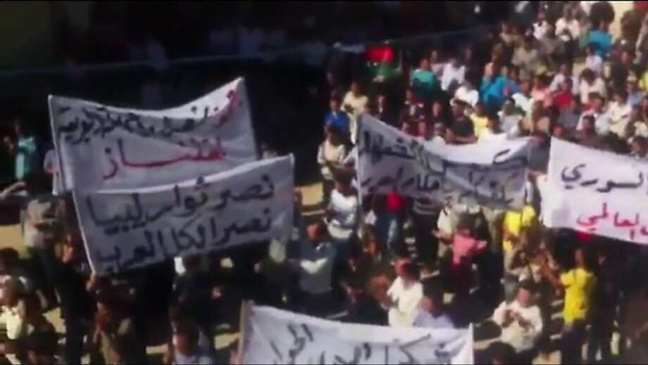 "In this image made from amateur video released by Ugarit News and accessed via The Associated Press Television News on Friday, Oct. 21, 2011, a banner at left, in Arabic, reads, ""the victory of the Libyan rebels is a victory for all Arabs."" in Idlib , Syria. (AP Photo/Ugarit News via APTN) THE ASSOCIATED PRESS CANNOT INDEPENDENTLY VERIFY THE CONTENT, DATE, LOCATION OR AUTHENTICITY OF THIS MATERIAL Photo: AP"
