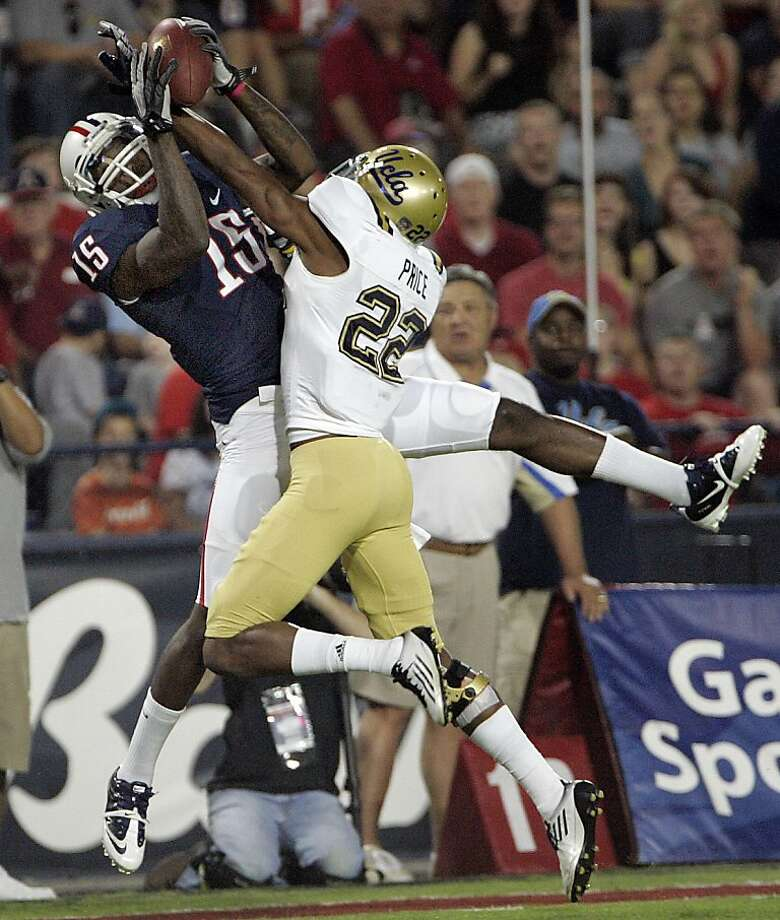 Arizona's Dan Buckner (15) catches the ball over UCLA's Sheldon Rice (22) for a touchdown during the first quarter of an NCAA college football game at Arizona Stadium in Tucson, Ariz., Thursday, Oct. 20, 2011. (AP Photo/Wily Low) Photo: Wily Low, AP