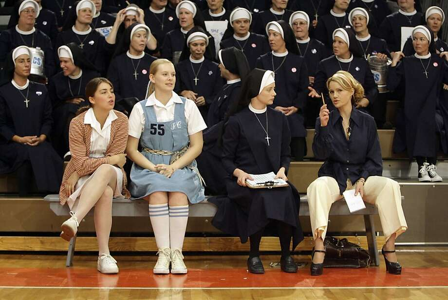 """FILE - In this June 15, 2007 file photo on the set of the film """"The Mighty Macs"""" shows from right to left are actresses Carla Gugino as coach Cathy Rush, Marley Shelton as Sister Sunday, Taylor Steel and Meghan Sabia in West Chester, Pa. The film  recounts the journey of the team Mighty Macs of tiny Immaculata College, which won the first national collegiate women's basketball championship in 1972. (AP Photo/Matt Rourke, File) Photo: Matt Rourke, AP"""