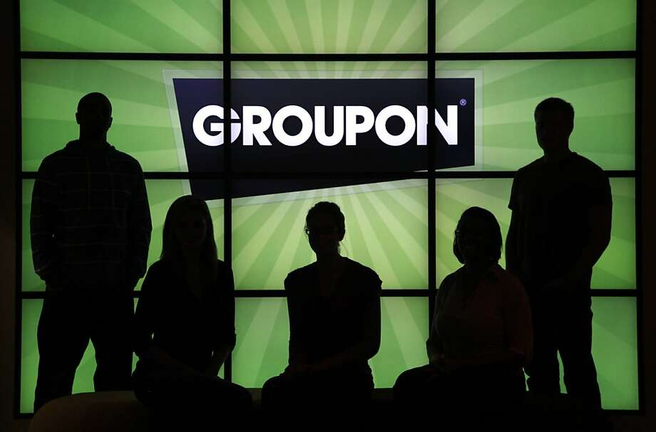 In this Sept. 22, 2011 photo, employees at Groupon pose in silhouette with the company logo in the lobby of the online coupon company's Chicago offices. Groupon (http://www.groupon.com) announced Wednesday, Sept. 28, 2011, Groupon Rewards, a new program allowing consumers to unlock specialGroupon deals from their favorite local businesses through repeat visits.  (AP Photo/Charles Rex Arbogast) Photo: Charles Rex Arbogast, AP