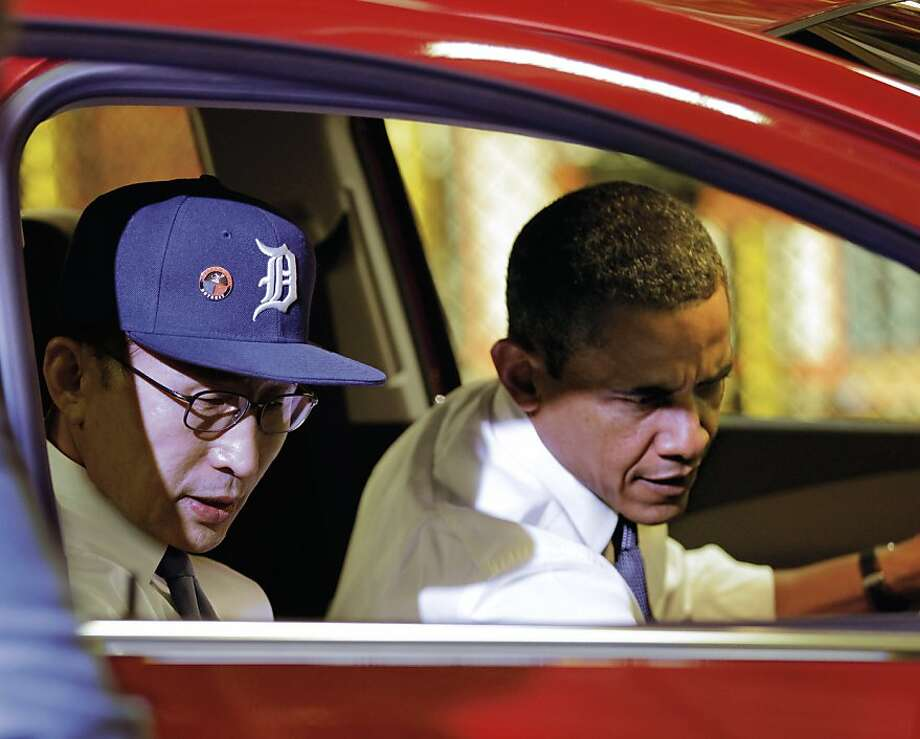 President Barack Obama and South Korean President Lee Myung-bak, wearing a Detroit Tigers baseball cap, check out the interior of the subcompact Chevrolet Sonic during a tour of the General Motors Orion Assembly Plant in Lake Orion, Mich., Friday, Oct. 14, 2011, to promote the free trade agreement between Washington and Seoul that was passed by Congress this week. (AP Photo/J. Scott Applewhite) Photo: J. Scott Applewhite, AP