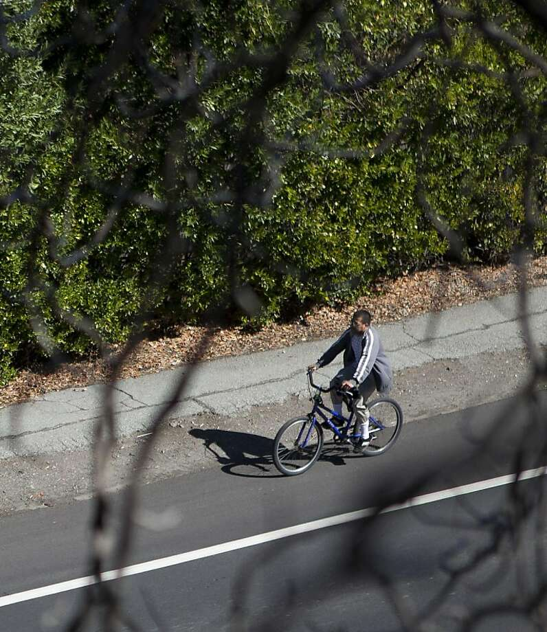 A cyclist peddles along the side of the Alpine Road bike path that Stanford University has proposed to front the bill for repaving on Friday, October 7, 2011 in Menlo Park, Calif. Photo: John Sebastian Russo, Special To The Chronicle