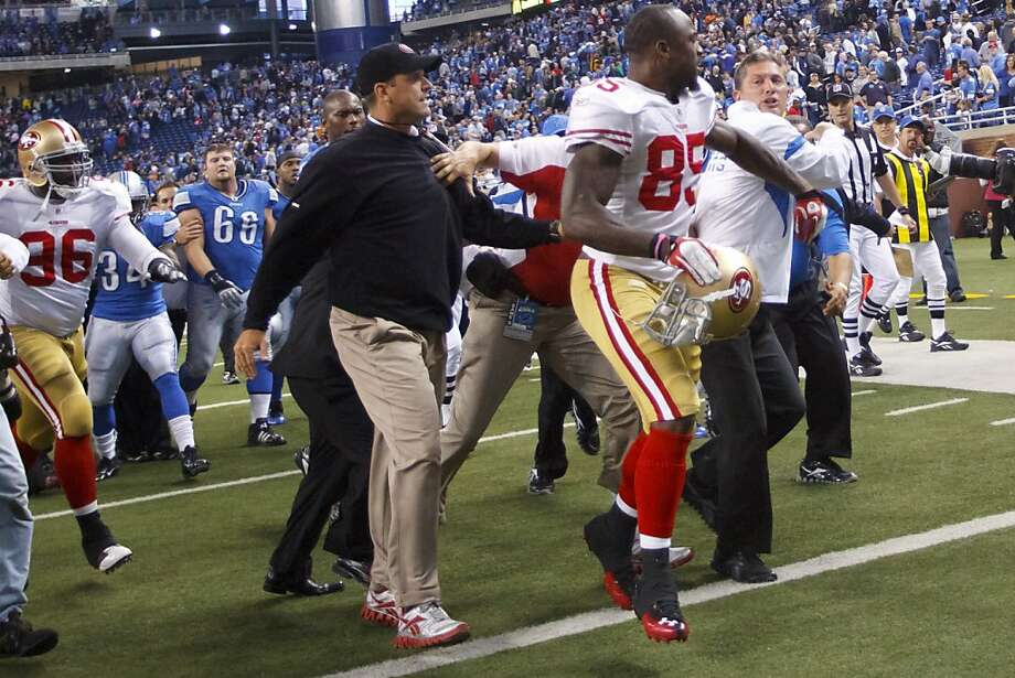 FIEL - This Oct. 16, 2011 photo shows San Francisco 49ers' Venron Davis (85), between 49ers coach Jim Harbaugh, left, and Detroit coach Jim Schwartz,  after  an NFL football game,  in Detroit. After the 49ers knocked Detroit from the unbeaten ranks 25-19 in a game that matched the pregame hype, both coaches bumped each other in an emotionally charged exchange.  (AP Photo/Rick Osentoski, File) Photo: Rick Osentoski, AP
