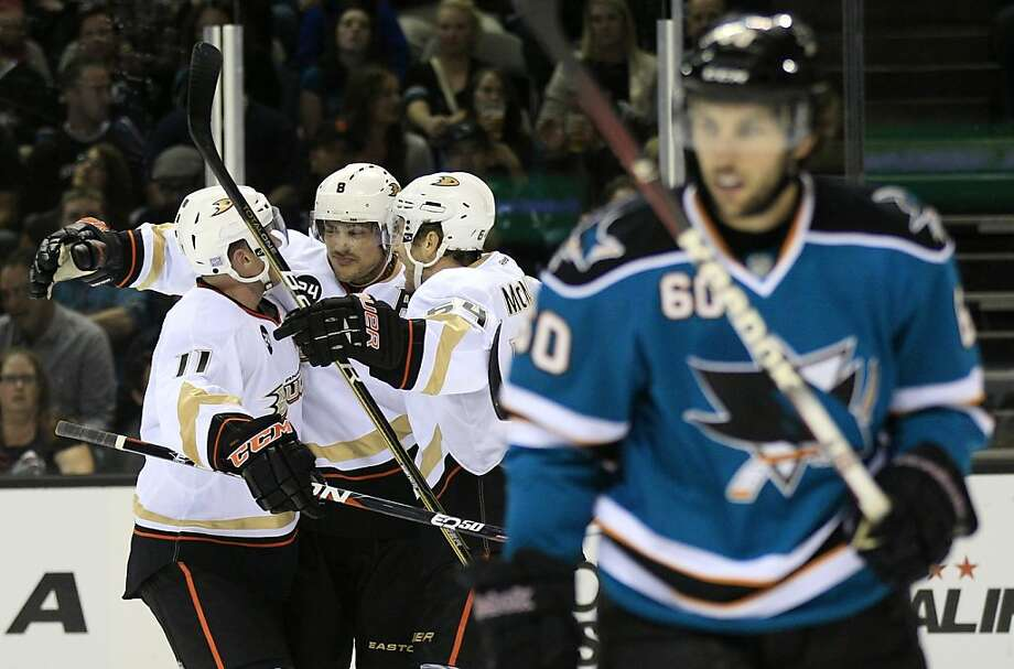 Anaheim Ducks right wing Teemu Selanne, center, of Finland, is hugged by teammates Saku Koivu (11), of Finland, and Brandon McMillan (64) as San Jose Sharks defenseman Jason Demers (60) skates away following Selanne's second goal of the first  period of an NHL hockey game in San Jose, Calif., Monday, Oct. 17, 2011. (AP Photo/Marcio Jose Sanchez) Photo: Marcio Jose Sanchez, AP
